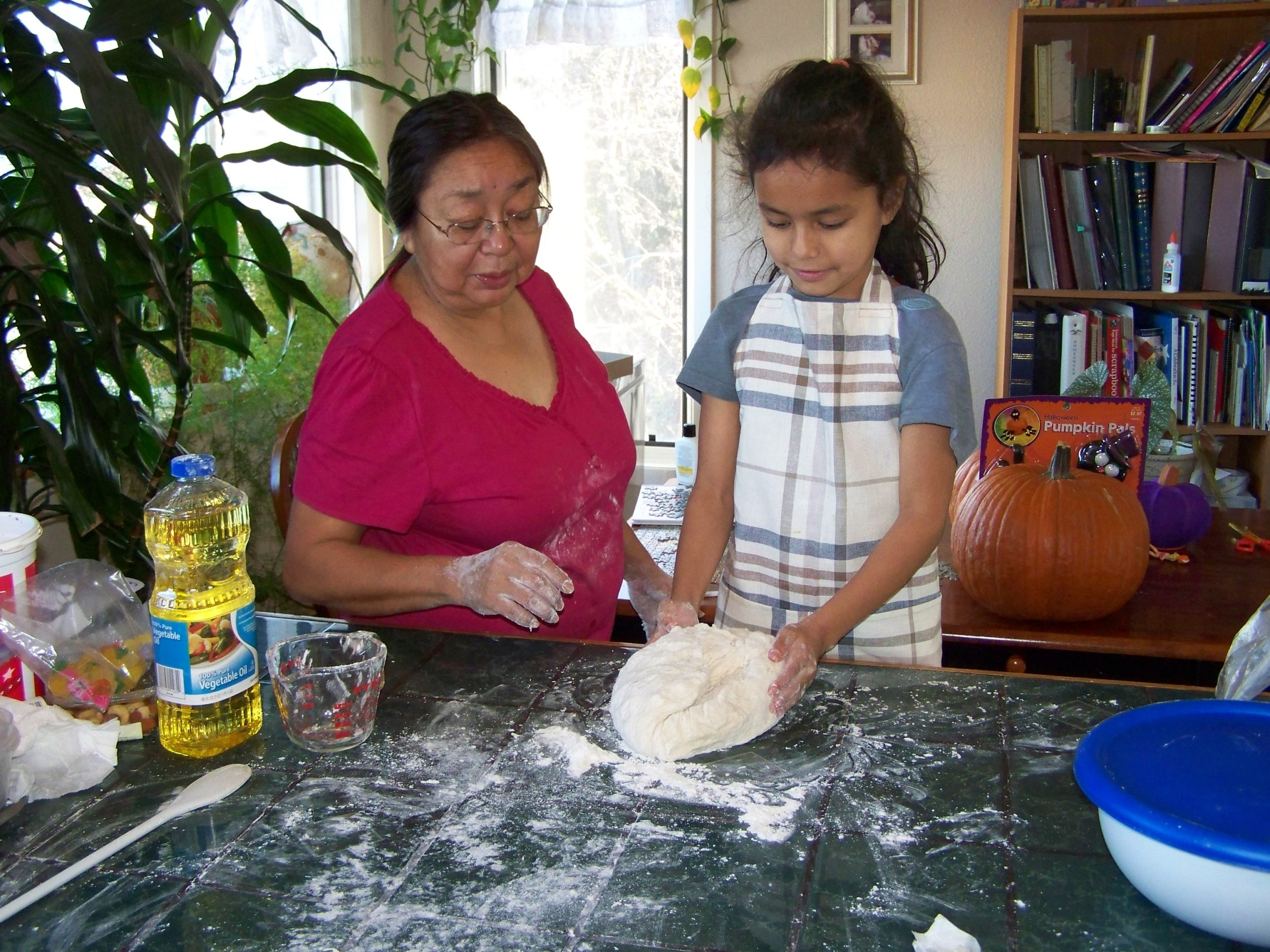 A grandmother teaches her granddaughter how to make bread