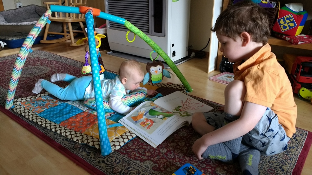 A child reads to an infant