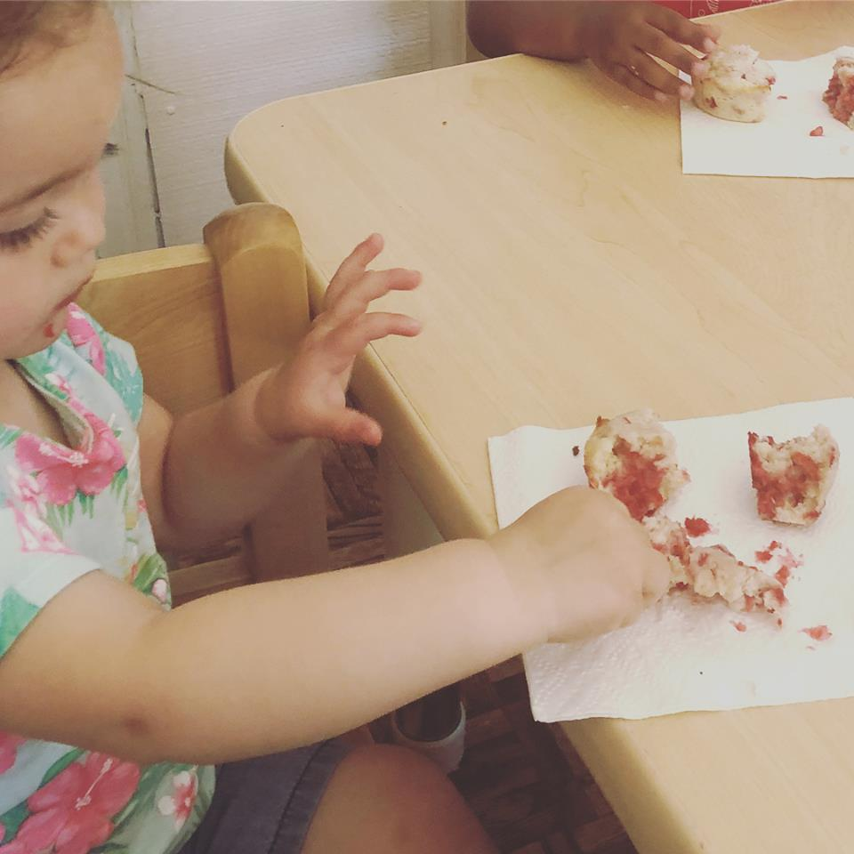 A child eats a berry muffin