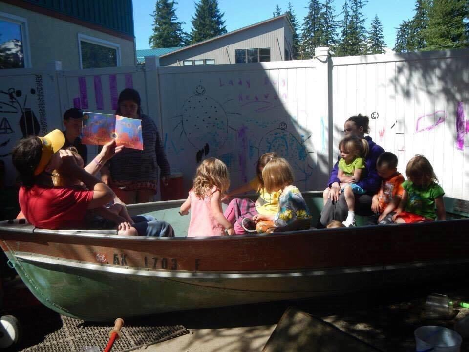 An adult reads to children in a boat