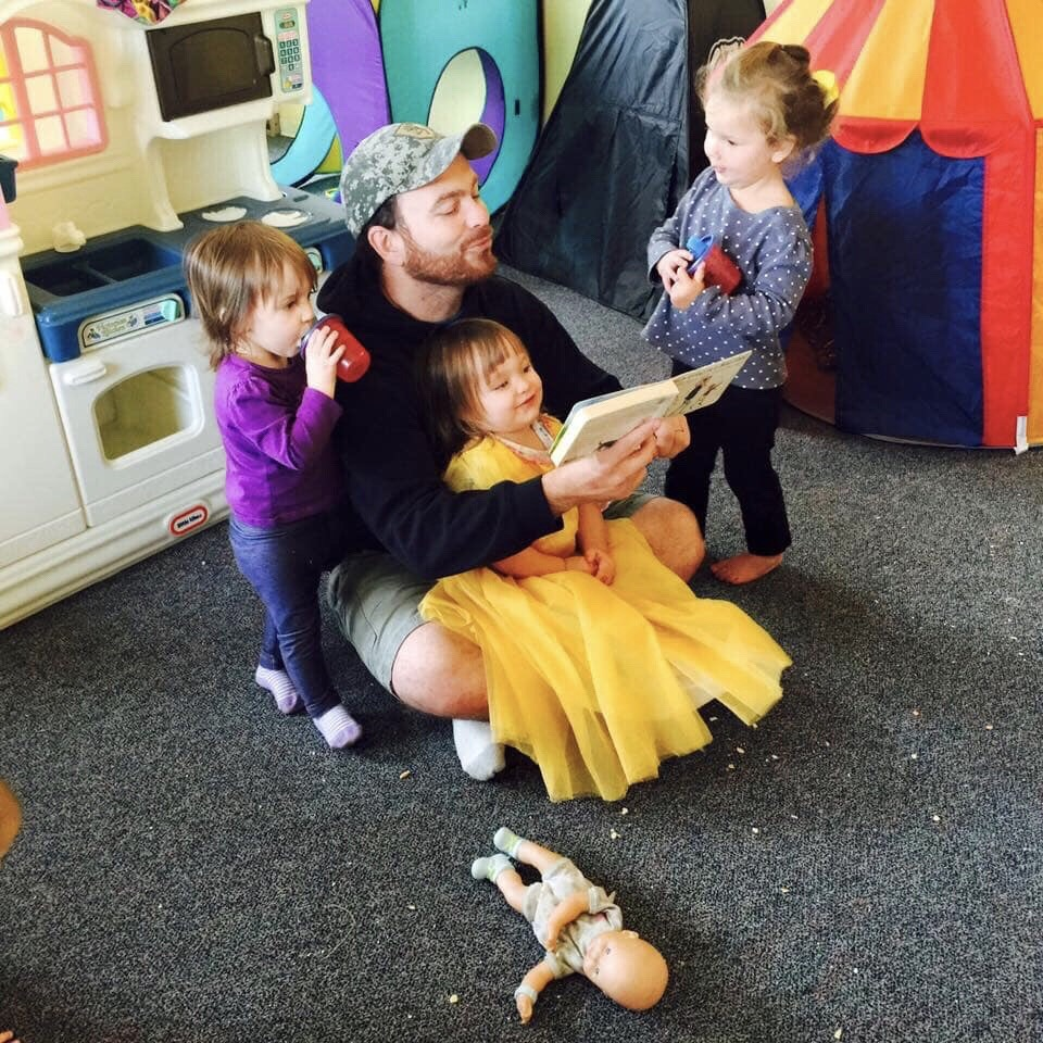 An adult reads with three small children