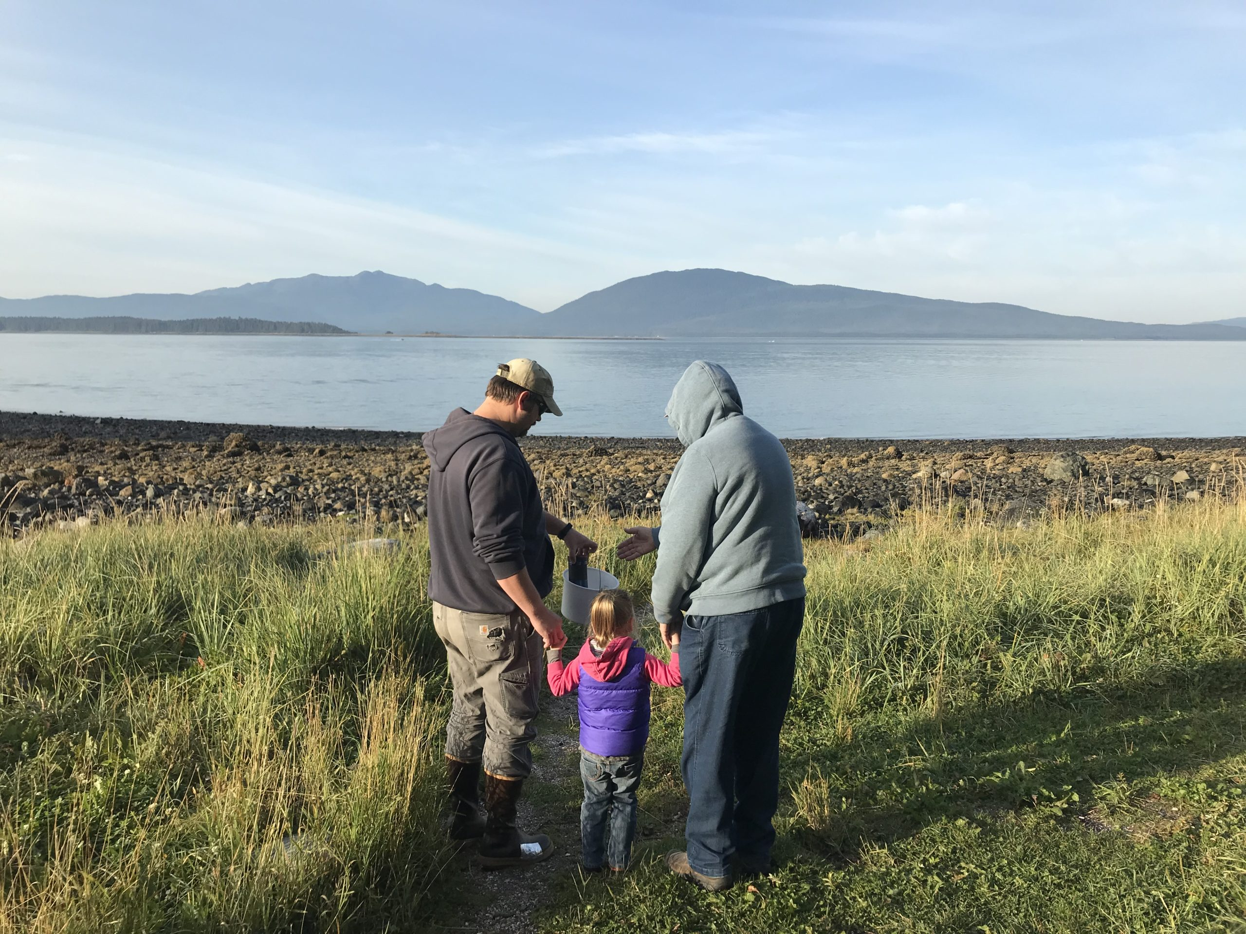 A family with a young child looks at a scenic vista