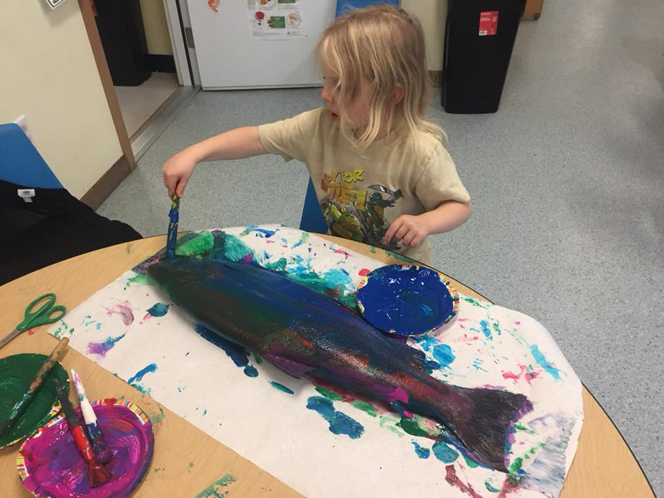 A child makes a fish print with paint